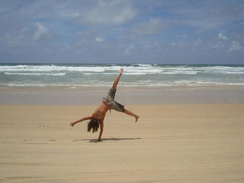 woman cartwheeling, cartwheelon beach