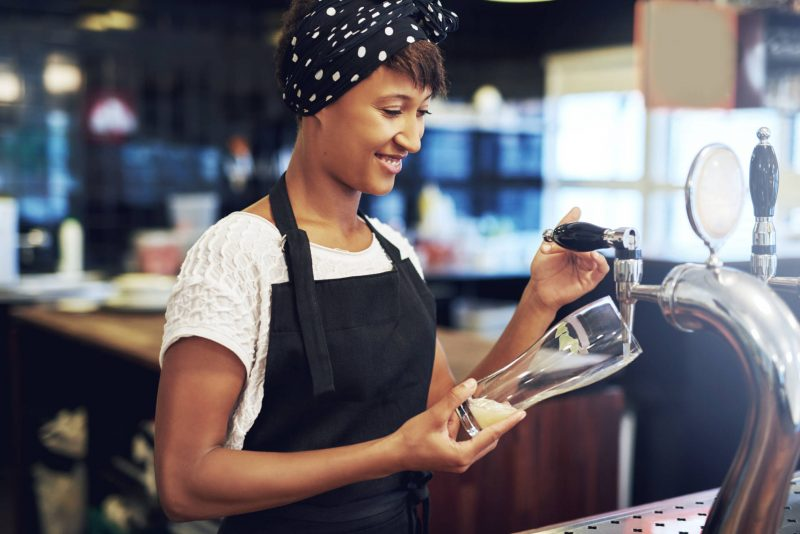 Young attractive female African American bartender pouring a glass of draft beer from the keg dispensing it from a tap behind the counter with a smile
